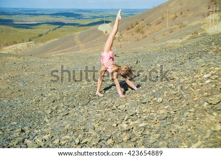 Mystic pictures, ballet gymnastic dancer woman girl stands on the cliff edge on one leg. mountain and forest in perspective. pink dress. - stock photo