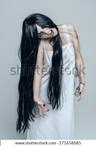 Mystical beautiful angry screaming woman on gray background - stock photo