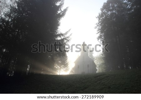 Mystical church in the forest and sun rays in morning - stock photo