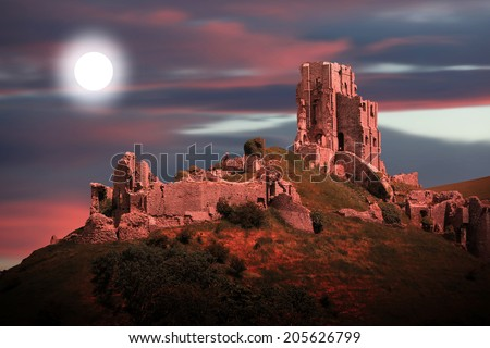 mystical corfe castle by moonlight and dramatic sunset sky - stock photo