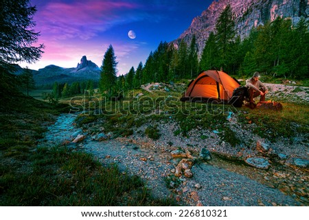 Mystical night landscape, in the foreground hike, campfire and tent - stock photo