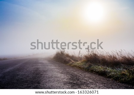 mystical rural foggy road going to the sunrise - stock photo