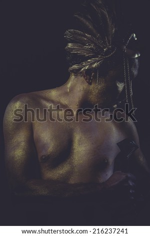 mythology golden bodypaint, man with gold helmet, ancient warrior deity - stock photo