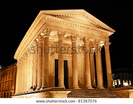 """Nîmes (France) - Roman Temple: the """"Maison Carrée"""" of Nîmes (Gard, France) built a few decades B.C. On this image it has been recently renovated and is lit up at night. - stock photo"""