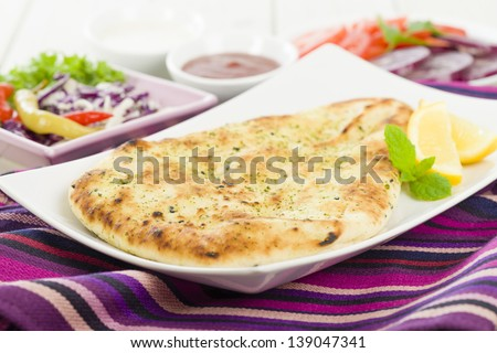 Naan Bread - Garlic and coriander flatbread with lemon wedges and salad on background. - stock photo