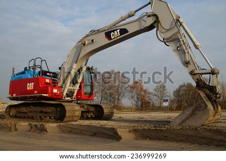 Naarden, THE NETHERLANDS - DECEMBER 5, 2014: caterpillar (CAT) excavator sits at rest on a construction site - stock photo