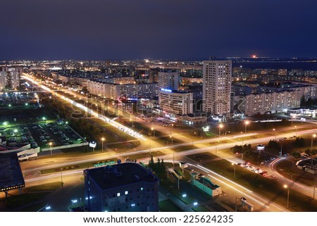 Naberezhnye Chelny, Russia - October 7, 2014: city night lights with the urban skyline and dramatic clouds in the night sky on the horizon