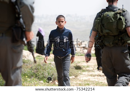 NABI SAMUEL, OCCUPIED PALESTINIAN TERRITORIES - APRIL 1: A Palestinian boy walks among Israeli soldiers in the West Bank town of Nabi Samuel on April 1, 2011. - stock photo