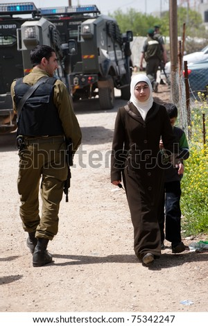 NABI SAMUEL, OCCUPIED PALESTINIAN TERRITORIES - APRIL 1: A Palestinian woman and boy walk among Israeli soldiers and military vehicles in the West Bank town of Nabi Samuel on April 1, 2011. - stock photo