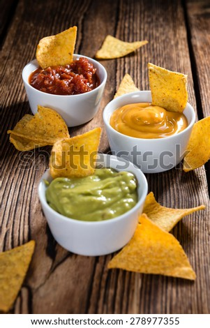 Nacho Dips (Salsa, Guacamole and Cheese) on wooden background - stock photo