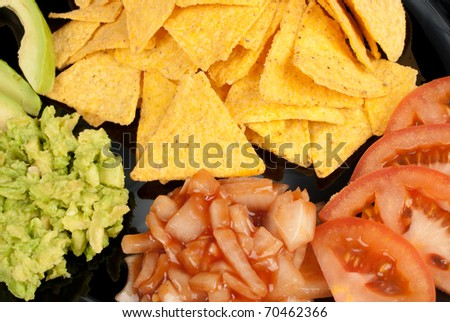 Nacho tortilla chips with dips and tomato - stock photo