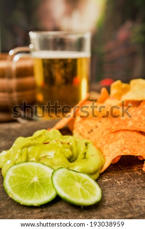 nachos and beer served on a wooden table - stock photo