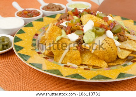 Nachos - Cheesy nachos served with sour cream, refried beans, salsa, jalapenos and guacamole on a colorful background - stock photo