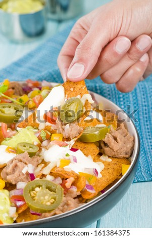 Nachos - Cheesy nachos topped with sour cream, refried beans, pico de ...