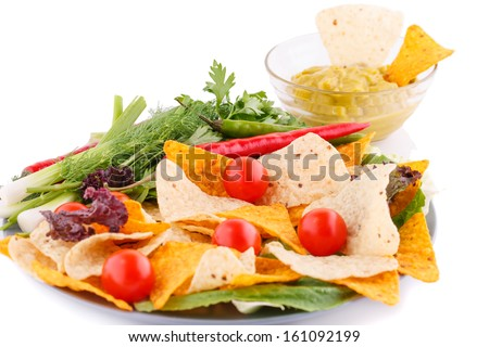 Nachos, cherry tomatoes, lettuce, herbs in plate on white background.