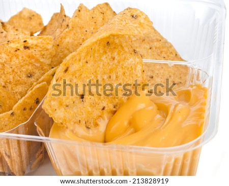 nachos chips with cheese sauce in plastic container  close up on white background - stock photo