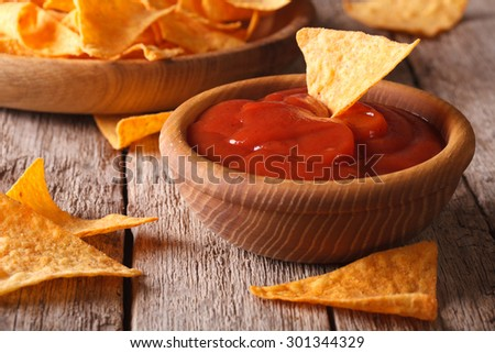 Nachos corn chips with spicy sauce closeup on the table. horizontal