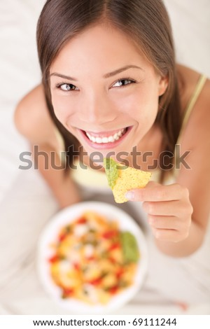 Nachos eating woman smiling looking at camera. Beautiful cute girl enjoying snacks in bed - white background. - stock photo