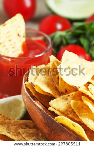 Nachos in wooden bowl with sauce, tomatoes and lime, selective focus
