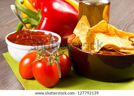 nachos on the table with tomatoes, pepper and oil
