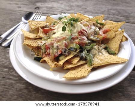 Nachos on white plate on wooden table - stock photo