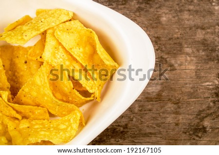 nachos served on a plate on a wood background - stock photo