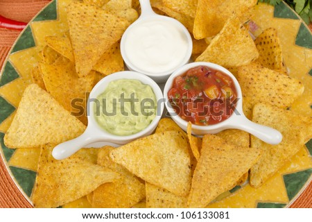 Nachos - Tortilla chips served with guacamole, sour cream and salsa dips. - stock photo