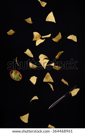 Nachos tortilla corn chips with fresh guacamole sauce flying, black background. - stock photo