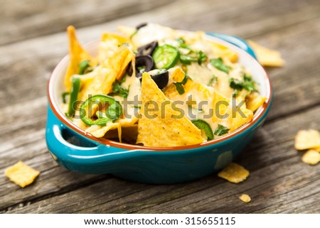 Nachos with melted cheese and salsa, guacamole and cheese dips - stock photo