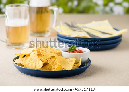 Nachos with salsa and sour cream dips at beer pub garden