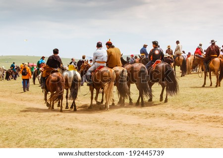 NADAAM HORSE RACE OUTSIDE ULAANBAATAR, MONGOLIA - JULY 12, 2010: Horseback spectators at the most important festival of the year in Mongolia from 11-13 July.