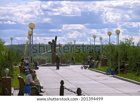 Nadym, Russia - June 13, 2005: City street. City Park and the monument in the center in Nadym, Russia - June 13, 2005. Strangers walking through the Park.
