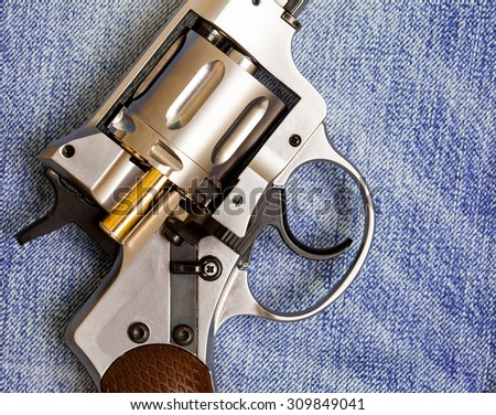 Nagan revolver with cartridge on blue jeans background, close-up, part of - stock photo