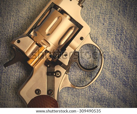 Nagan revolver with cartridge on blue jeans background, close-up, part of. instagram image filter retro style - stock photo