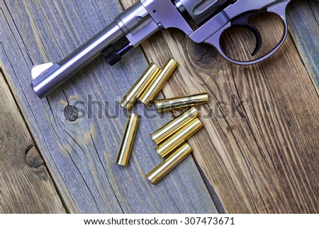 Nagan revolver with cartridges on aged wood background, close-up, part of - stock photo