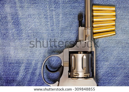 Nagan revolver with cartridges on blue jeans background, close-up, part of - stock photo