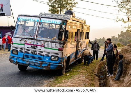 NAGARKOT, NEPAL - MARCH 27, 2014: tire change of an old public bus during sunset