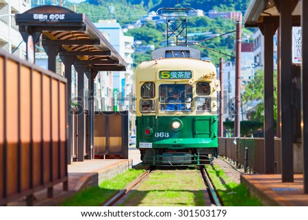 NAGASAKI, JAPAN - 16 SEPTEMBER 2013: Green Public tram moving along the railway. Nagasaki city, Japan. - stock photo