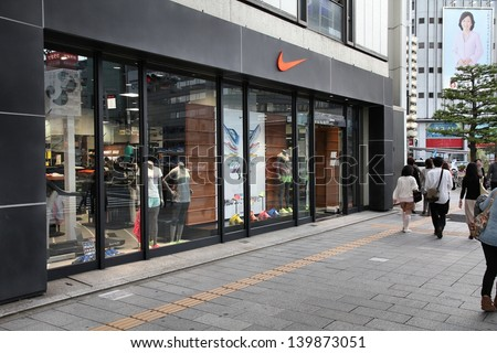 NAGOYA, JAPAN - MAY 3: People walk past Nike store on May 3, 2012 in Nagoya, Japan. Nike is one of most recognized fashion brands. It exists since 1964 and had US$ 19 billion revenue (2010). - stock photo