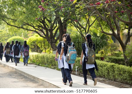 NAGPUR, MAHARASHTRA, INDIA, 9 APRIL 2016 : unidentified group of young girl  students walking together, Rear view of university students with backpacks walking on campus road