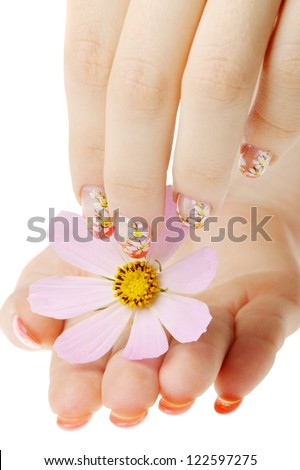 Nail art. Female nails with figure of a camomile close up above a flower - stock photo