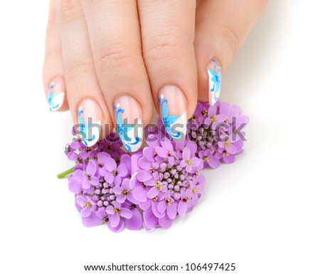 Nail art. Female nails with figure of petal blue color closeup and flower - stock photo