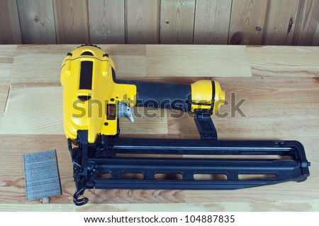 Nail gun and nails on wood background - stock photo