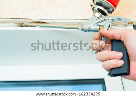 Nail gun being used to install trim around plastic window in doors - stock photo