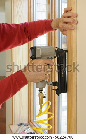Nail gun being used to install wood trim around windows with finishing nails - stock photo