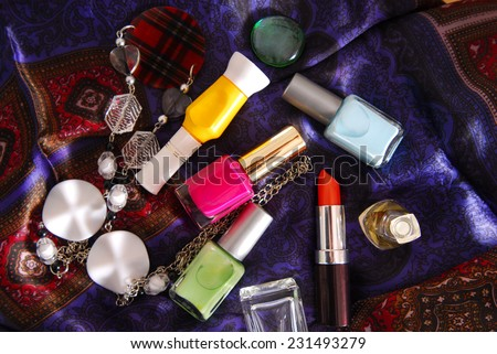 nail polish and accessory on silky scarf - stock photo