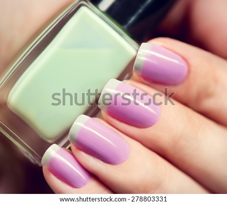 Nail Polish. Art Manicure. Nail Polish. Beauty hands. Trendy Stylish Colorful Nails and Nailpolish bottle closeup - stock photo
