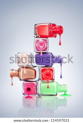 Nail polish dripping from stacked bottles. - stock photo