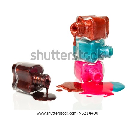 Nail polish dripping from stacked bottles isolated on white