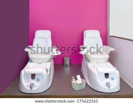 Nail saloon Pedicure chair spa furniture in pink purple wall - stock photo